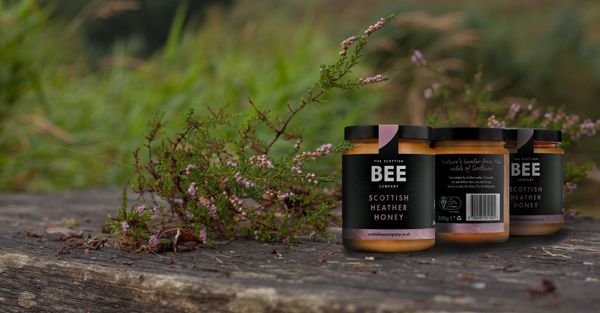 Three pots of Heather Hney from the Scottish Bee Company on a wooden bench with a bunch of heather.